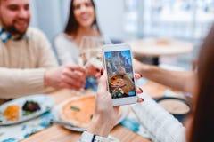 Weibliche Hand, die Foto von der Gruppe von Personen hat das Abendessen im Café macht lizenzfreie stockfotografie