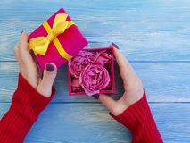 Weibliche Hand, die Geschenkbox mit romantischem Geburtstagsglückwunsch des Bogens, rosafarbene Blume auf blauem hölzernem Hinter lizenzfreies stockbild