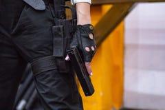 Weibliche Hand, die Gewehr, Abschluss hochhält Kriegs-Actionfilm-Art Lizenzfreie Stockfotos