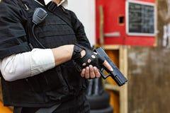 Weibliche Hand, die Gewehr, Abschluss hochhält Kriegs-Actionfilm-Art Lizenzfreie Stockbilder