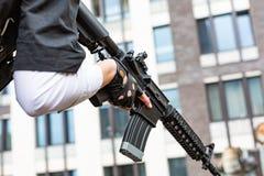 Weibliche Hand, die Gewehr, Abschluss hochhält Kriegs-Actionfilm-Art Lizenzfreies Stockfoto