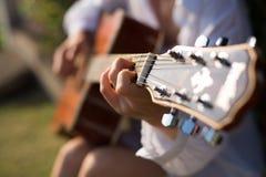 Weibliche Hand, die Gitarre spielt Lizenzfreies Stockfoto