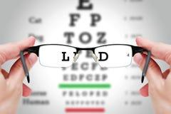 Weibliche Hand, die Gläser mit Sehvermögentest auf Diagrammbrett hält Stockbilder