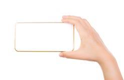 Weibliche Hand, die Goldhandy Smartphonemodelle hält Stockfoto
