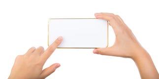 Weibliche Hand, die Goldhandy Smartphonespott hochhält Lizenzfreie Stockfotos