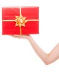 Weibliche Hand, die große rote Geschenkbox lokalisiert hält Stockbilder