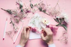 Weibliche Hand, die Grußkarte mit Umschlag mit Blumen macht Hochzeit, Einladung, Valentinstag, Mutter ` s Tageskonzept Flache Lag lizenzfreies stockbild