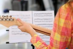 Weibliche Hand, die hölzernen Hals der E-Gitarre hält Stockfoto
