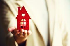 Weibliche Hand, die Hausschlüssel, Immobilienagentur hält Immobiliarversicherung, Sicherheit und gemütliches Hauptkonzept Kopiere Stockfotos