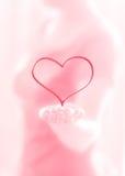 Weibliche Hand, die Herz auf einem rosa Hintergrund gibt Lizenzfreies Stockbild