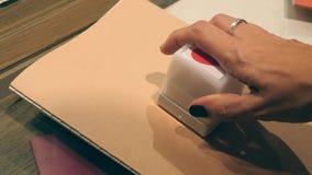 Weibliche Hand, die Herz-Druck-Stempel auf Notizbuch setzt 4K, Slowmotion stock footage