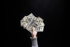 Weibliche Hand, die hundert Dollarschein auf schwarzem Hintergrund hält C Stockbild