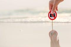 Weibliche Hand, die kein Fotozeichen auf dem Strand hält Stockbild