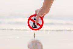 Weibliche Hand, die kein TelefonRufzeichen auf dem Strand hält Lizenzfreie Stockfotografie