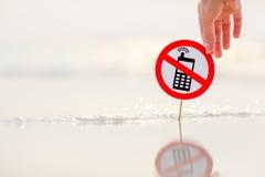 Weibliche Hand, die kein TelefonRufzeichen auf dem Strand hält Stockfoto