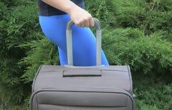 Weibliche Hand, die Koffer hält Stockbild