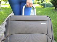Weibliche Hand, die Koffer hält Stockfotos