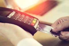 Weibliche Hand, die Kreditkarte in einen Leser einfügt lizenzfreie stockfotos