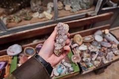 Weibliche Hand, die Kristallquarz Mineral mit Steinen auf den Regalen im Hausbergshop hält Lizenzfreie Stockbilder