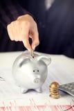 Weibliche Hand, die Münze in Sparschwein auf dem Schreibtisch einsetzt Stockfoto