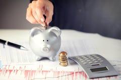 Weibliche Hand, die Münze in Sparschwein auf dem Schreibtisch einsetzt Lizenzfreie Stockfotografie