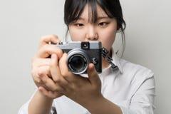 Weibliche Hand, die mirrorless Kamera der modernen Kamera hält Lizenzfreies Stockfoto