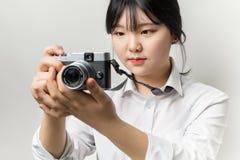 Weibliche Hand, die mirrorless Kamera der modernen Kamera hält Lizenzfreies Stockbild