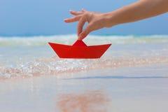 Weibliche Hand, die mit rotem Papierboot auf dem Strand spielt Lizenzfreies Stockbild