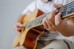 Weibliche Hand, die Musik durch Akustikgitarre - naher hoher Schuss spielt und Stockfotografie