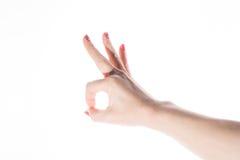 Weibliche Hand, die OKAYzeichen auf einem weißen Hintergrund zeigt Stockfotografie