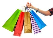 Weibliche Hand, die Papiereinkaufstaschen lokalisiert auf Weiß hält Stockfotografie