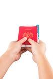 Weibliche Hand, die Pass und Währung IV hält Stockbild