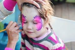 Weibliche Hand, die purpurroten Schmetterling auf Gesicht zeichnet Stockbild