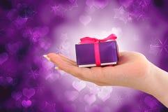 Weibliche Hand, die purpurrotes Geschenk anhält Stockbild