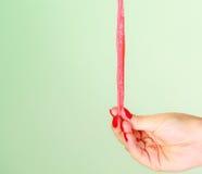 Weibliche Hand, die süße Lebensmittelgeleesüßigkeit auf Grün hält Stockfotos