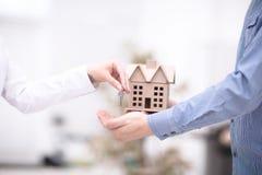 Weibliche Hand, die Schlüssel von der neuen Wohnung zur männlichen Hand auf Hintergrund gibt Stockfoto