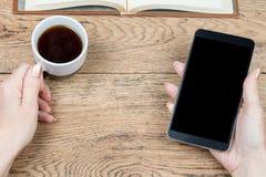 Weibliche Hand, die Smartphone und Kaffee hält Stockbild
