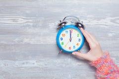 Weibliche Hand, die Uhr hält Lizenzfreies Stockfoto