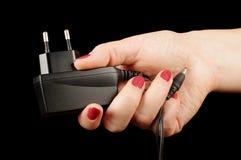 Weibliche Hand, die Wechselstrom-Ladegerätadapter hält Stockfotografie