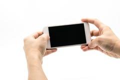 Weibliche Hand, die weißes Mobiltelefon mit schwarzem Schirm hält Lizenzfreie Stockfotos