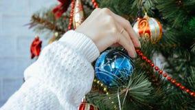 Weibliche Hand, die Weihnachtsbaum, Nahaufnahme verziert stockbild
