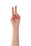 Weibliche Hand, die zwei Finger lokalisiert auf Weiß zeigt Lizenzfreies Stockfoto