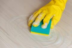 Weibliche Hand gelbes in der Handschuh-Reinigungs-Licht-hölzernen modernen Tabelle mit blauem Schwamm für Hauptwartung und Hausha Lizenzfreie Stockbilder