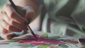 Weibliche Hand hält einen Malerpinsel, zeichnet in ein Album unter Verwendung des Scharlachrots Farbe stock video footage