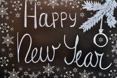 Weibliche Hand hält einen Weihnachtsball auf einer Tafel mit einem Aufschrift guten Rutsch ins Neue Jahr Lizenzfreies Stockbild
