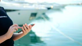 Weibliche Hand h?lt Smartphone auf unscharfem Hintergrund des Hafens mit Yachten lizenzfreie stockfotos