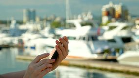 Weibliche Hand h?lt Smartphone auf unscharfem Hintergrund des Hafens mit Yachten stockbilder