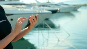 Weibliche Hand h?lt Smartphone auf unscharfem Hintergrund des Hafens mit Yachten stockfoto