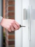 Weibliche Hand halten Schlüssel, um in Türschloss einzufügen Stockbild