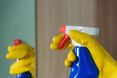 Weibliche Hand im gelben Handschuh-Reinigungs-Spiegel mit Spray-Reiniger in der Portugiesischen Galeere Hausarbeit, Spring Cleani lizenzfreie stockbilder